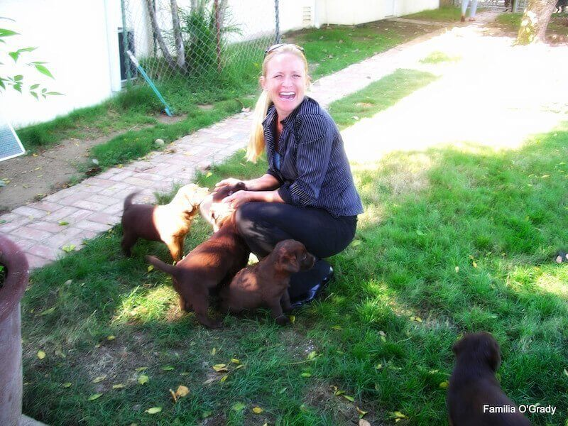 Female blonde Mom playing with puppies